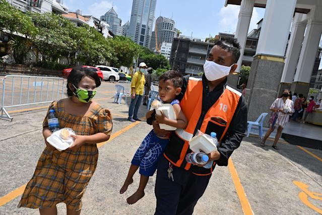 People wear masks after collecting food donations in Bangkok. (Getty Images)