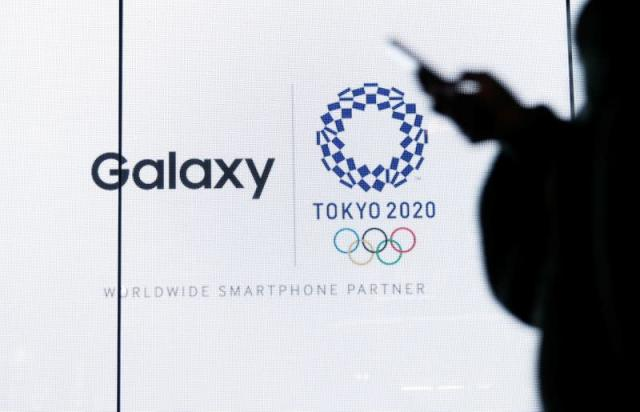 A woman uses her smartphone as an electric screen displaying logos of Tokyo 2020 Olympic Games and Galaxy at Galaxy Harajuku in Tokyo