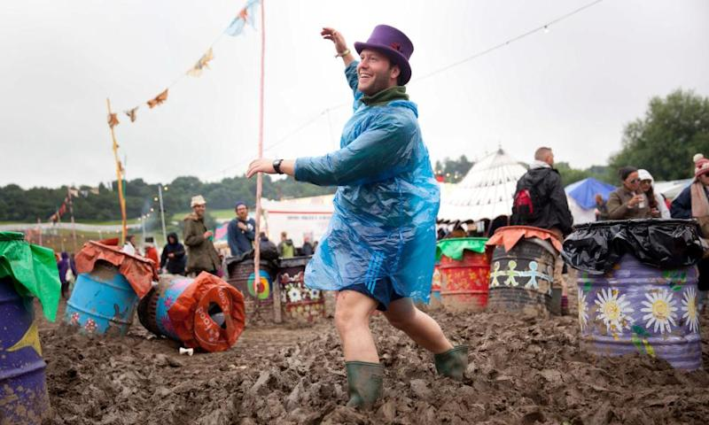 Man in a top hat and a plastic mac dances ankle-deep in mud at Glastonbury 2016