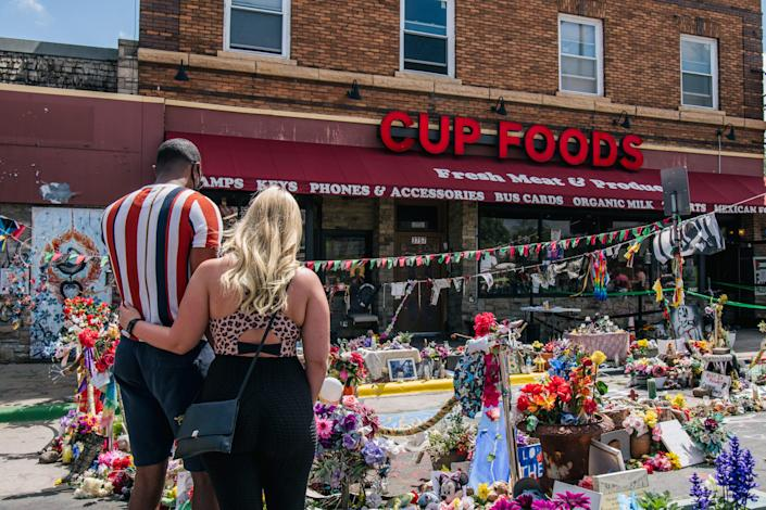 A couple pay their respects to George Floyd at the intersection of 38th Street and Chicago Avenue on May 25 in Minneapolis. Around the USA, groups honored George Floyd, who was murdered by Minneapolis police officer Derek Chauvin on May 25, 2020.