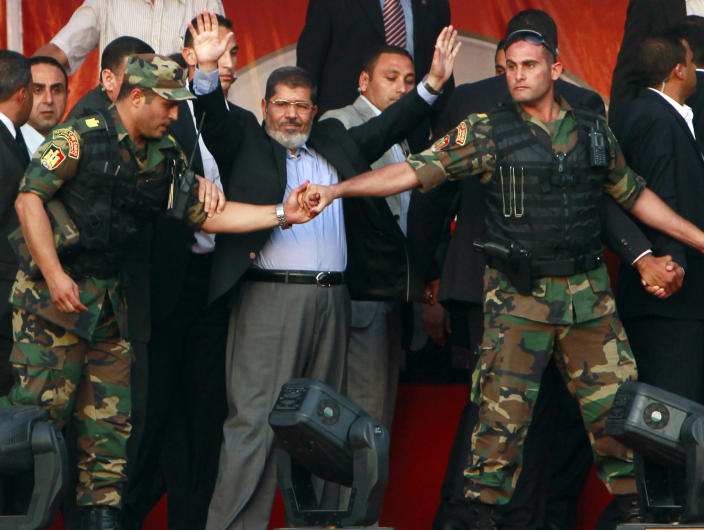 Egypt's Islamist President-elect Mohammed Morsi waves to supporters while surrounded by presidential guards in Cairo's Tahrir Square in June 2012. (Photo: Amr Abdallah Dalsh/Reuters)