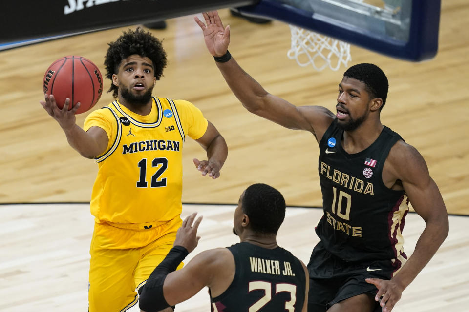 Michigan guard Mike Smith (12) drives to the basket over Florida State guard M.J. Walker (23) and forward Malik Osborne (10) during the second half of a Sweet 16 game in the NCAA men's college basketball tournament at Bankers Life Fieldhouse, Sunday, March 28, 2021, in Indianapolis. (AP Photo/Darron Cummings)