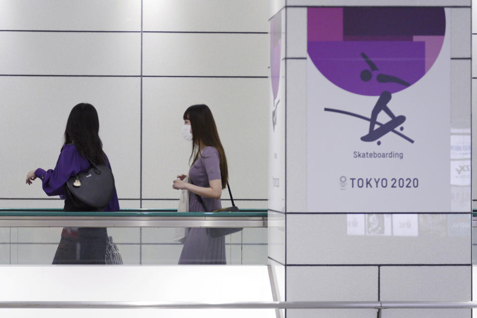 People wearing protective masks to help curb the spread of the coronavirus walk near a Tokyo 2020 Olympic Games advertisement Tuesday, June 22, 2021, in Tokyo. (AP Photo/Eugene Hoshiko)