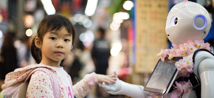 A child shaking hands with an android robot.