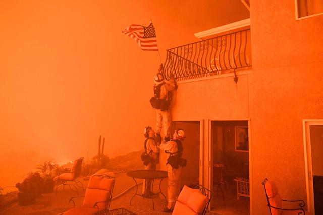 """<p>JUL. 8, 2017 – Firefighters remove a US flag as flames from the """"Wall Fire"""" close in on a luxury home in Oroville, California on July 8, 2017.<br> The first major wildfires after the end of California's five-year drought raged across the state on July 8, as it was gripped by a record-breaking heatwave. (Photo: Josh Edelson/AFP/Getty Images) </p>"""