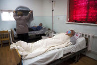 A woman covers her husband, who is suspected of having coronavirus, with a blanket in an infectious diseases clinic in Stepanakert, the separatist region of Nagorno-Karabakh, Tuesday, Oct. 20, 2020.Nagorno-Karabakh, which lies within Azerbaijan but has been under the control of ethnic Armenian forces since a war there ended in 1994, faces an outbreak of the coronavirus amid the largest outbreak of hostilities in more than a quarter-century. (AP Photo)