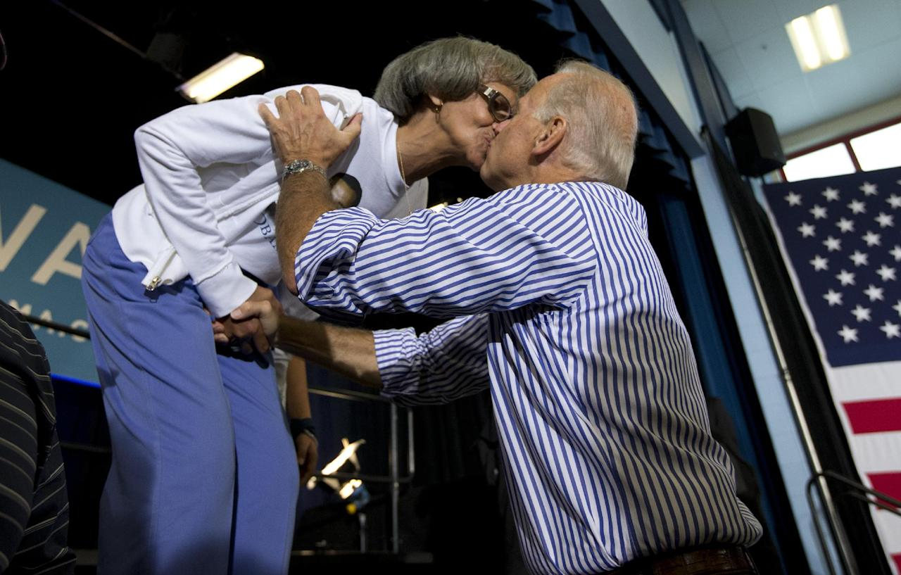 FILE - In this Sept. 8, 2012 file photo, Vice President Joe Biden kisses a supporter during a campaign event in Zanesville, Ohio. Obama goes airborne in a doozie of a bear hug with a pizza guy in Florida. Joe Biden cozies up with a biker chick in Ohio. Even the more reserved Mitt Romney seems to be loosening up some with people he meets on the campaign trail. Kissing babies and slapping backs are so yesterday. The 2012 candidates are putting their all into the campaign cliche of pressing the flesh. (AP Photo/Carolyn Kaster, File)