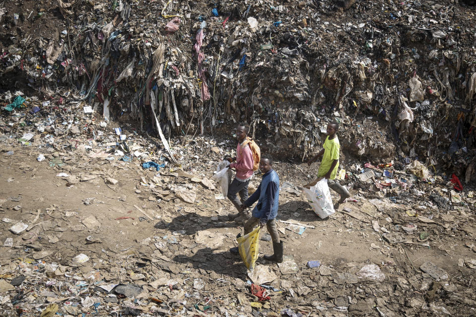 Mohamed Nassur, 17, left, Peter Kihika, 16, center, and Dominic Munyoki, 15, right, scavenge for scrap metal to sell at Kenya's largest landfill Dandora where Mohamed now works after his mother lost her job and his school was closed due to the coronavirus pandemic, in Nairobi, Kenya Saturday, Sept. 26, 2020. The United Nations says the COVID-19 pandemic risks significantly reducing gains made in the fight against child labor, putting millions of children at risk of being forced into exploitative and hazardous jobs, and school closures could exacerbate the problem. (AP Photo/Brian Inganga)