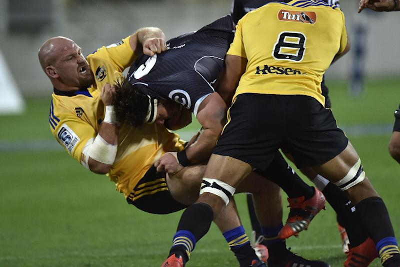 Sharks' left flanker Marcell Coetzee (C) is tackled by Hurricanes' tighthead prop Ben Franks (L) and Victor Vito (R) during the Super 15 Rugby Union match between the Wellington Hurricanes and RSA Sharks at Westpac Stadium in Wellington on May 9, 2015. AFP PHOTO / MARTY MELVILLE (AFP Photo/Marty Melville)