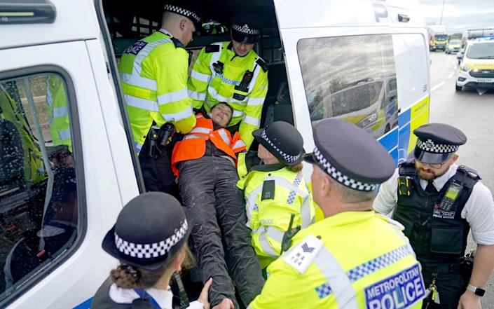 A protester from Insulate Britain is carried by police officers into a police van - PA