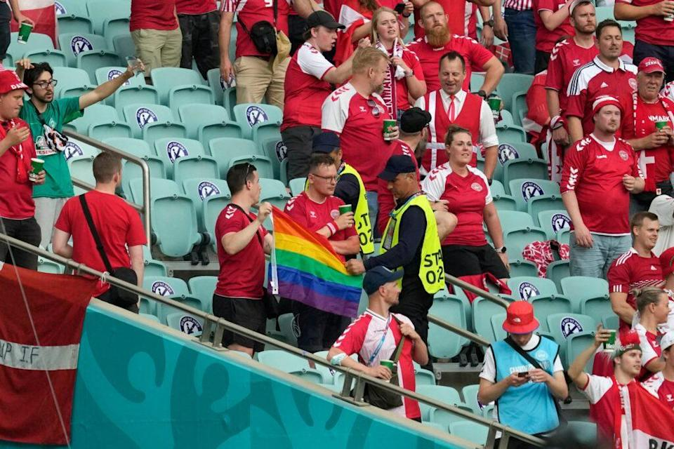 Stewards intervene on a Denmark supporter who was holding up a rainbow flag before the UEFA EURO 2020 quarter-final football match between the Czech Republic and Denmark at the Olympic Stadium. (Darko Vojinovic / POOL / AFP) (Photo by DARKO VOJINOVIC/POOL/AFP via Getty Images)