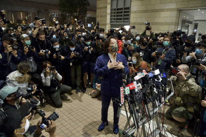 Lawrence Lau, center, one of the 47 pro-democracy activists charged with conspiracy, gestures outside a court after being released in Hong Kong Friday, March 5, 2021. Four of the 47 pro-democracy activists charged with conspiracy to commit subversion were released on bail Friday, after prosecutors dropped an appeal against the court's decision to grant them bail. (AP Photo/Vincent Yu)