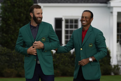 Tiger Woods stands next to Masters champion Dustin Johnson with his green jacket after his victory at the Masters golf tournament Sunday, Nov. 15, 2020, in Augusta, Ga. (AP Photo/Chris Carlson)
