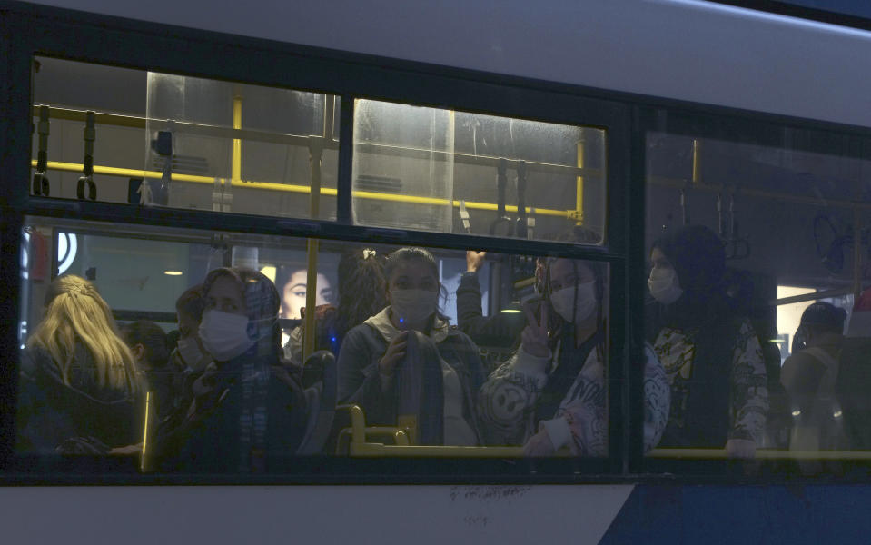 FILE - In this Thursday, Nov. 12, 2020, file photo, commuters wearing masks to help protect against the spread of coronavirus, travel in a bus in Ankara, Turkey. When Turkey changed the way it reports daily COVID-19 infections, it confirmed what medical groups and opposition parties have long suspected — that the country is faced with an alarming surge of cases that is fast exhausting the Turkish health system. The official daily COVID-19 deaths have also steadily risen to record numbers in a reversal of fortune for the country that had been praised for managing to keep fatalities low. With the new data, the country jumped from being one of the least-affected countries in Europe to one of the worst-hit. (AP Photo/Burhan Ozbilici, File)