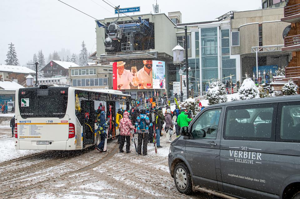 VERBIER, SWITZERLAND - DECEMBER 29: Skiers exit the bus to enter the queue for cabin transport on December 29, 2020 in Verbier, Switzerland. Most British tourists are said to have left the ski resorts after Covid-19 quarantine restrictions were introduced by the Swiss government on December 21 due to a new variant of the coronavirus found in the UK. (Photo by Robert Hradil/Getty Images)
