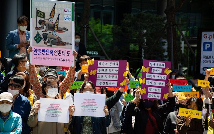South Korean supporters of former 'comfort women' rally against the Japanese government in Seoul - Shutterstock