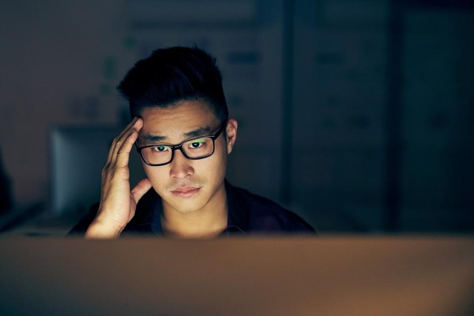 Shot of a young businessman looking stressed while using a computer at night in a modern office