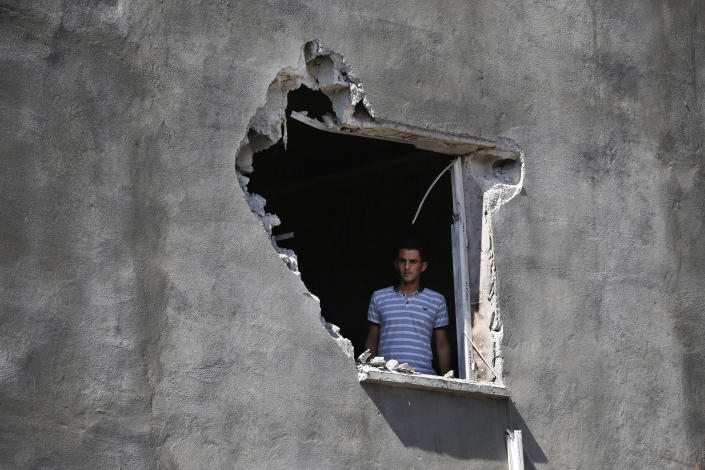 A local resident looks out from a hole on a house that was damaged by a mortar fire from inside Syria, on the Turkish town of Akcakale, southeaster, Turkey, Saturday, Oct. 12, 2019.Nobody got hurt by the attack.The owners of the house weren't home at the time of the attack. Turkey's military said it captured a key Syrian border town under heavy bombardment Saturday as its offensive against Kurdish fighters pressed into its fourth day with little sign of relenting despite mounting international criticism. (AP Photo/Lefteris Pitarakis)