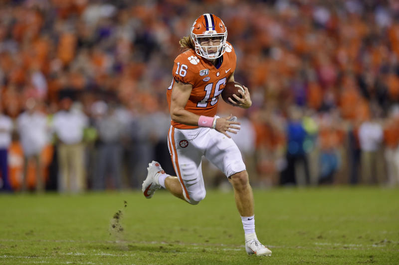 Trevor Lawrence runs with the ball in his hands.
