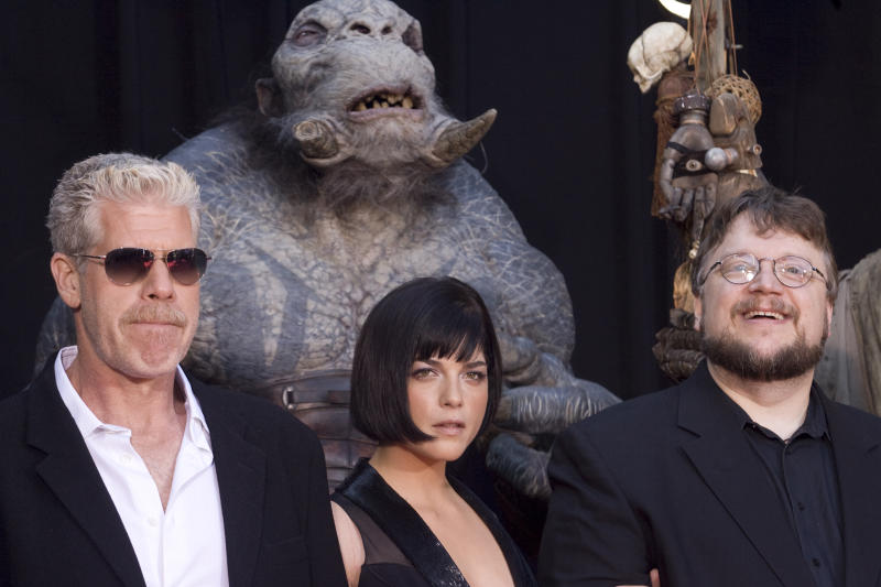 "Director Guillermo del Toro (R), actress Selma Blair (C) and actor Ron Perlman pose for photographers surrounded by the characters from the movie ""Hellboy II The Golden Army"" during the premiere of the film in Los Angeles, California, June 28, 2008. REUTERS / Hector Mata (UNITED STATES)"