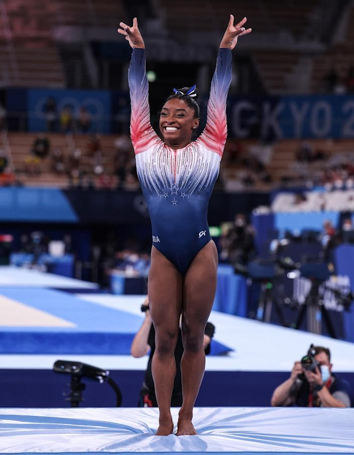 Simone Biles, smiling, stands on the mat with both arms lifted.