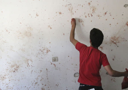 A man cleans bloodstains off a wall of a shop at a site hit by what activists said were barrel bombs dropped by forces loyal to Syria's President Assad in Kfar Zeita village in the central province of Hama