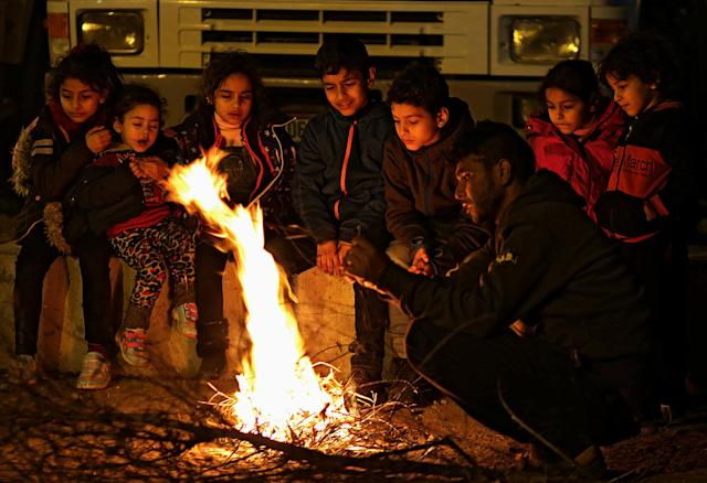<p>Palestinians travellers' children warm themselves by a fire while they wait with their families to cross into Egypt through Rafah border crossing between Gaza Strip and Egypt in the southern Gaza Strip, Feb. 7, 2018. (Photo: Mohammed Saber/EPA-EFE/REX/Shutterstock) </p>