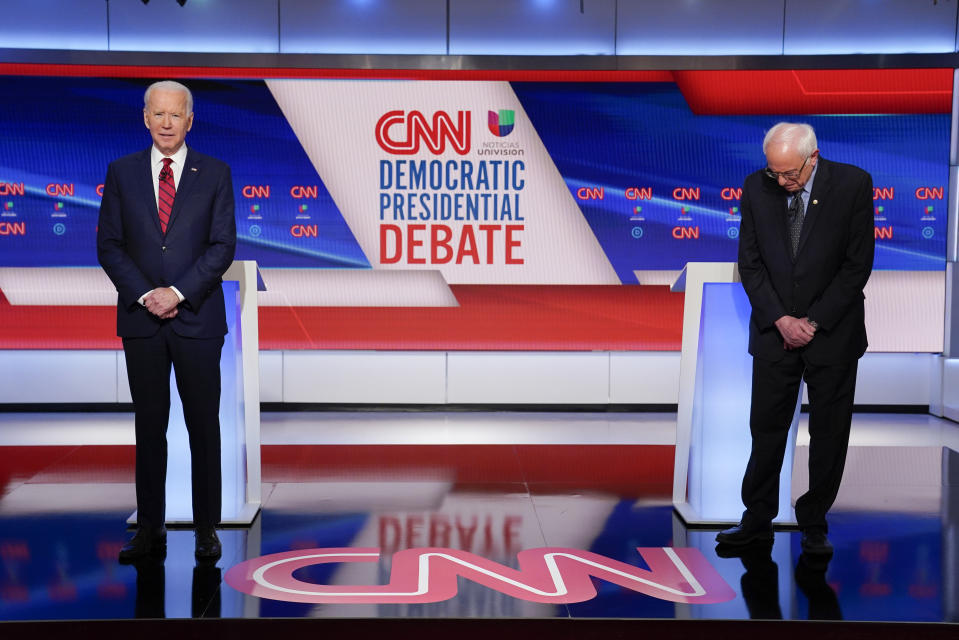 Former Vice President Joe Biden, left, and Sen. Bernie Sanders, I-Vt., right, wait on stage to participate in a Democratic presidential primary debate at CNN Studios in Washington, Sunday, March 15, 2020. (AP Photo/Evan Vucci)