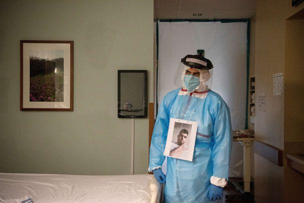 PHOTO: Fernando Olvera wears a picture around his neck for patients to know what he looks like while wearing personal protective equipment as he visits the room of a COVID-19 patient at United Memorial Medical Center in Houston, Texas, July 25, 2020. (Callaghan O'hare/Reuters)
