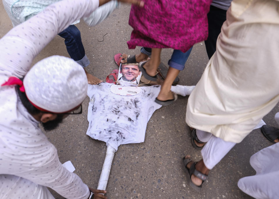 Supporters of Islamist parties stomp on a portrait of French President Emmanuel Macron during a protest after Friday prayers in Dhaka, Bangladesh, Friday, Oct. 30, 2020. Thousands of Muslims and activists marched through streets and rallied across Bangladesh's capital on Friday against the French president's support of secular laws that deem caricatures of the Prophet Muhammad as protected under freedom of speech. (AP Photo/Mahmud Hossain Opu)