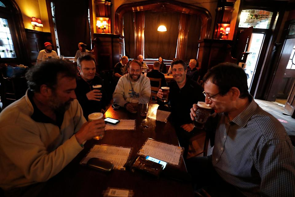 <p>People enjoying a drink at The Forester pub in Ealing on Monday evening</p> (AP)