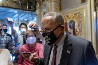 Senate Majority Leader Sen. Chuck Schumer of N.Y., walks out of a Senate Democratic meeting pumping his fist at the Capitol in Washington, Wednesday, Oct. 6, 2021, as a showdown looms with Republicans over raising the debt limit. (AP Photo/Andrew Harnik)