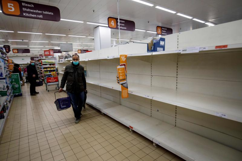 People shop in aisles with empty shelves in a Sainsbury's supermarket in Walthamstow, east London on March 20, 2020. - The British prime minister urged people in his daily press conference on March 19 to be reasonable in their shopping as supermarkets emptied out of crucial items -- notably toilet roll -- across Britain. The government said it was temporarily relaxing elements of competition law to allow supermarkets to work together to maintain supplies. (Photo by Tolga AKMEN / AFP) (Photo by TOLGA AKMEN/AFP via Getty Images)