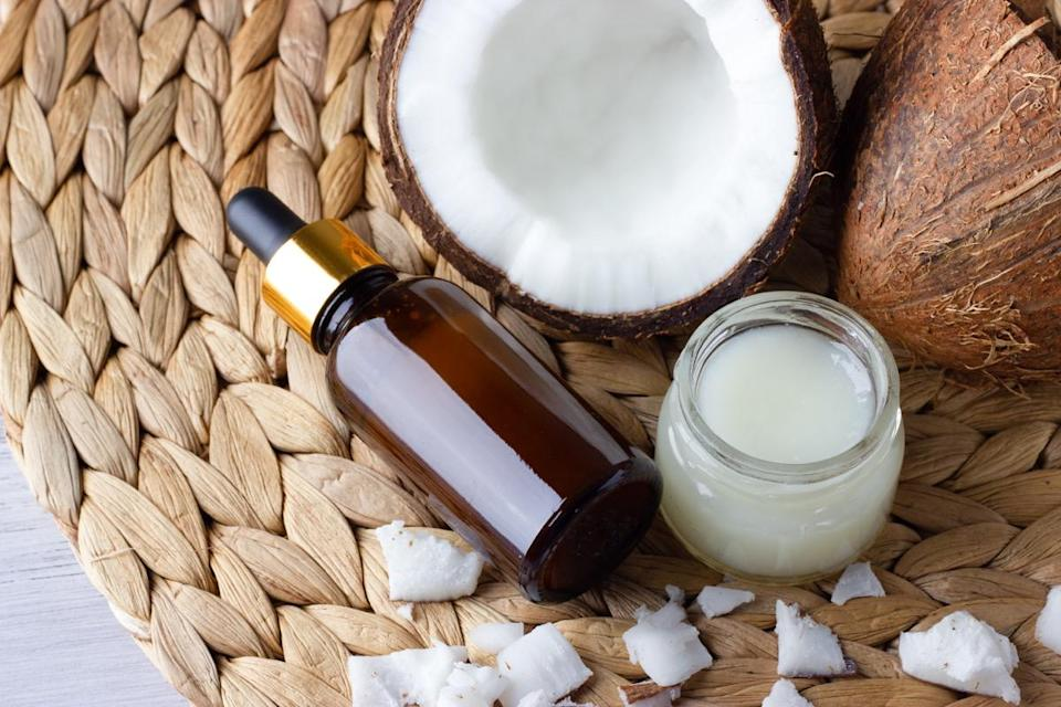 Coconut oil and fresh coconuts on the wooden table