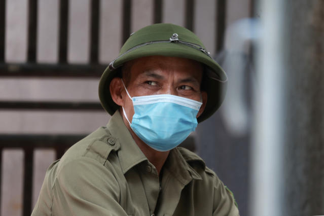 A militia officer guards the barricaded entrance of an alley where one of its residents is suspected to have COVID-19 in Hanoi, Vietnam on Wednesday, July 29, 2020. Vietnam intensifies protective measures as the number of locally transmissions, starting at a hospital in the popular beach city of Da Nang, keeps increasing since the weekend. (AP Photo/Hau Dinh)