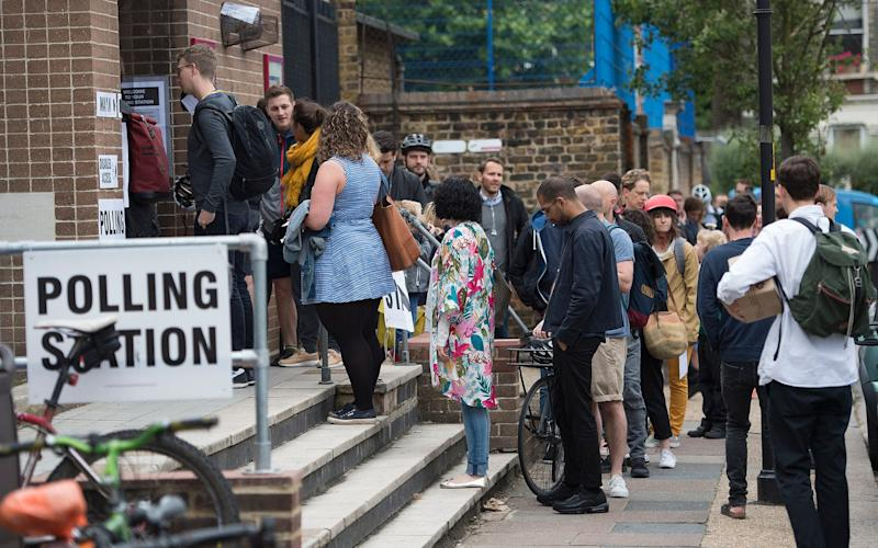 People queue to cast their vote at a Polling station in Peckham South London. - Eddie Mulholland