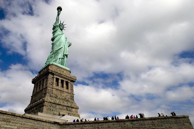 Tourists visit the Statue of Liberty in New York Harbor, Sunday, Oct. 13, 2013, in New York. The Statue of Liberty reopened to the public after the state of New York agreed to shoulder the costs of running the site during the partial federal government shutdown. (AP Photo/John Minchillo)