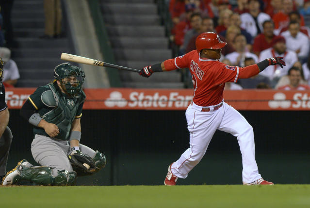 Los Angeles Angels' Erick Aybar, right, hits Oakland Athletics catcher Derek Norris in the head with a bat during a swing in the fourth inning of a baseball game, Tuesday, June 10, 2014, in Anaheim, Calif. (AP Photo/Mark J. Terrill)