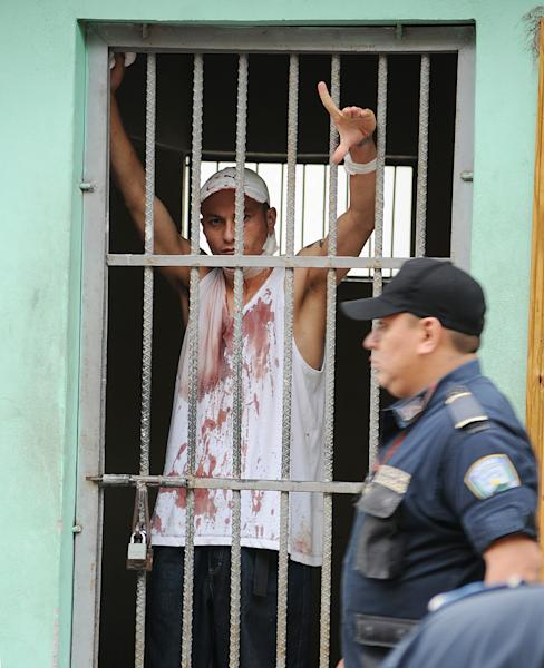 A Honduran police officer walks past an injured prisoner, flashing a gang sign from inside a cell at the Hospital Escuela, in Tegucigalpa, Honduras, Saturday, Aug. 3, 2013.Honduran President Porfirio Lobo ordered the militarization of the country's main prison on Saturday after a riot there left at least three gang members dead and three guards injured. Police said members of the 18 gang clashed with common criminals in Honduras' National Penitentiary, located 10 miles (15 kilometers) north of the capital. (AP Photo/Fernando Antonio)