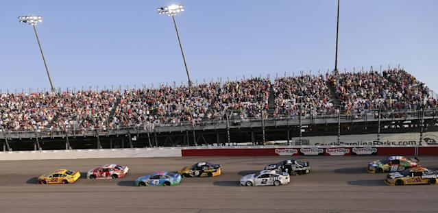 Joey Logano (22) leads the field into Turn 1 during the NASCAR Sprint Cup auto race at Darlington Speedway in Darlington, S.C., Saturday, April 12, 2014. (AP Photo/Chuck Burton)