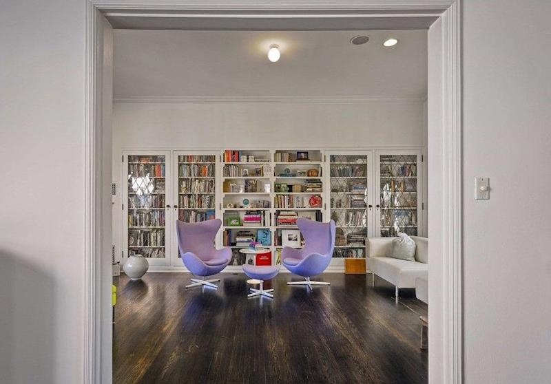 A view of a library shows white shelves filled with books with two Modernist chairs in lavender.