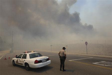 A police officer mans a roadblock as smoke billows from a wildfire driven by fierce Santa Ana winds in Rancho Cucamonga, California April 30, 2014. REUTERS/David McNew