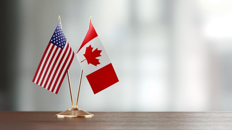 American and Canadian flag pair on desk over defocused background. Horizontal composition with copy space and selective focus.