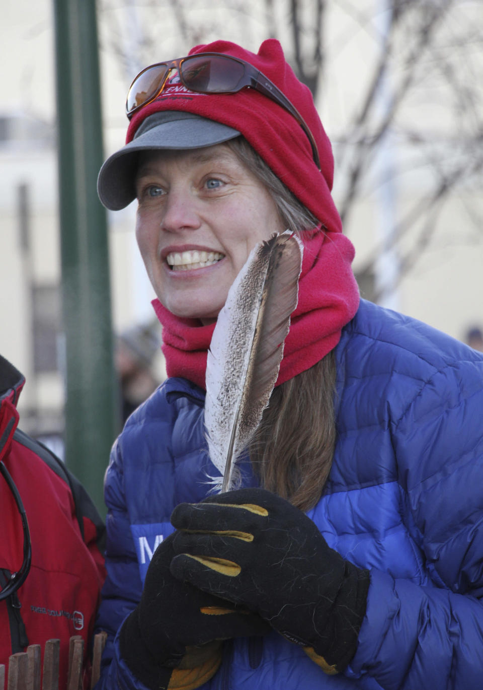 In this Saturday, March 2, 2019, photo, musher Aliy Zirkle, holds a feather given to her as a gift by a fan at the ceremonial start of the Iditarod Trail Sled Dog Race in Anchorage, Alaska. Zirkle was leading the race early Thursday, March 7, 2019, and was the first musher to reach the halfway point of the race when she pulled into the checkpoint in the ghost town of Iditarod, Alaska. (AP Photo/Mark Thiessen)