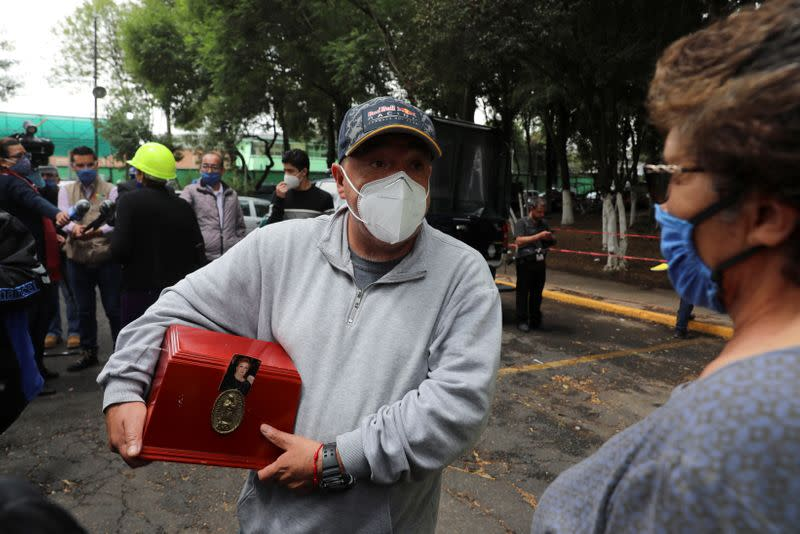Resident Carlos Rodriguez Delgado holds a box with his mother's ashes outside an apartment building damaged by an earthquake that struck southern Mexico on Tuesday, in Mexico City