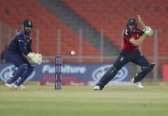 England's Jos Buttler, right, plays a shot during the fifth Twenty20 cricket match between India and England at Narendra Modi Stadium in Ahmedabad, India, Saturday, March 20, 2021. (AP Photo/Ajit Solanki)