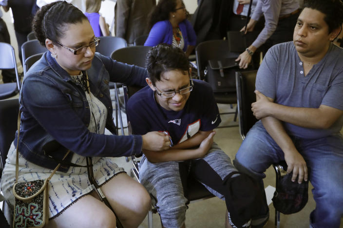 Gary Sanchez, of Honduras, right, watches as his wife, Mariela comforts their son, Jonathan, 16, during a news conference, Monday, Aug. 26, 2019, in Boston. The Sanchez family came to the United States seeking treatment for Jonathan's cystic fibrosis. Doctors and immigrant advocates say federal immigration authorities are unfairly ordering foreign born children granted deferred action for medical treatment to return to their countries. (AP Photo/Elise Amendola)