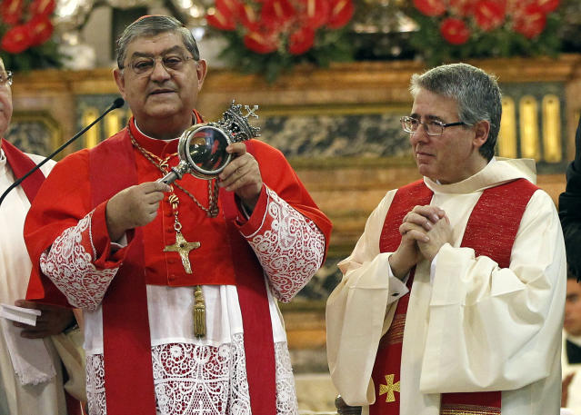 Archbishop of Naples, Cardinal Crescenzio Sepe (L) holds a flask believed to contain drops of liquefied blood of San Gennaro in Naples Cathedral, Italy, in this September 19, 2013 file photo. (Ciro Luca / Reuters)