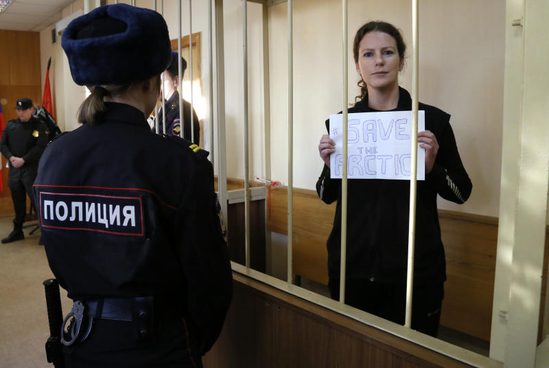 Greenpeace International activist Ana Paula Alminhana Maciel of Brazil holds a poster during a court hearing that considers investigators request to extend the detention of 30 members of the Arctic Sunrise Greenpeace International ship in St.Petersburg, Russia, Monday, Nov. 18, 2013. The 30 people arrested following a Greenpeace protest at an Arctic oil rig were transferred to St. Petersburg from Murmansk. (AP Photo/Dmitry Lovetsky)