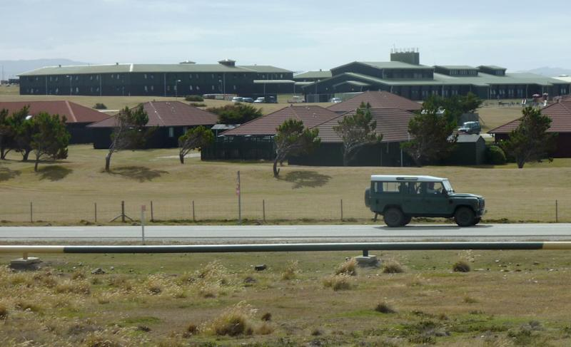 In this Sunday March 4, 2012 photo, a vehicle drives past British military housing where Prince William is living, top, in Mount Pleasant, Falkland Islands. The William-and-Kate refrigerator magnets in the gift shops are about as close as most people here have come to spotting the future king of England, who has only strolled through town once so far during his six-week tour of duty in the Falklands. (AP Photo/Michael Warren)